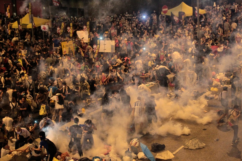 Protesters flee from teargas fired by riot police, during clashes after thousands of protesters blocked the main street to the financial Central district outside the government headquarters in Hong Kong